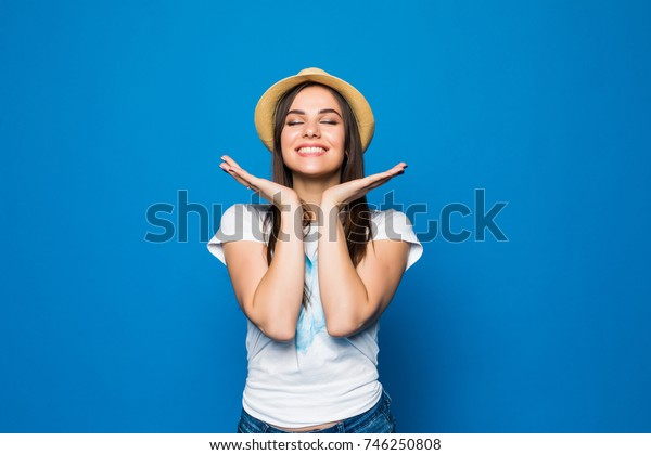 Close up portrait of a happy excited young woman in beach hat looking at camera isolated over blue background