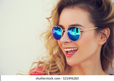 Close Up Portrait of Happy Fashion Woman in Sunglasses. Smiling Trendy Girl in Summer. Laughing Female. White Wall Background Copy Space. Not Isolated Toned Photo.