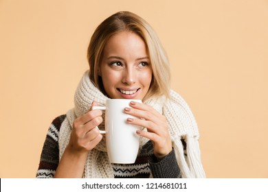 Close up portrait of a happy girl dressed in sweater and scarf isolated over beige background, having cup of hot tea, looking away