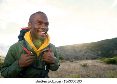 Close up portrait of happy hiker walking with backpack in nature