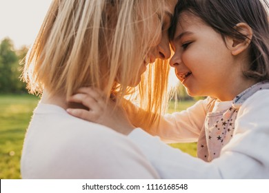 Close up portrait happy kid playing with mother outdoor. Portrait of joyful woman and her cute child playing and hug in the park outside. Happy love emotion. Happy Mothers Day.Motherhood and childhood