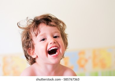 Close up portrait of happy little boy kid laughing. Smiling cute toddler.