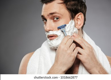 Close up portrait of happy man looking on camera and shaving his face with razor isolated over gray background