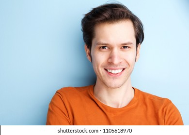 Close up portrait of happy man in orange shirt on blue background