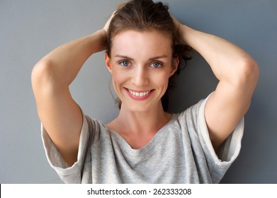 Close up portrait of a happy mid adult woman smiling with hands in hair against gray background
