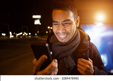 Close up portrait of happy middle aged asian man looking at his mobile phone and smiling outdoors in city at night