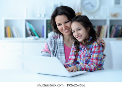 Close up portrait of happy mother and daughter using laptop together