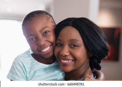 Close up portrait of happy mother and daughter at home