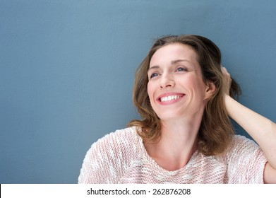 Close up portrait of a happy older woman laughing with hand in hair