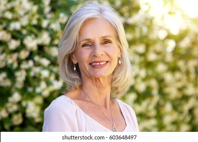 Close up portrait of happy older woman standing outside in summer
