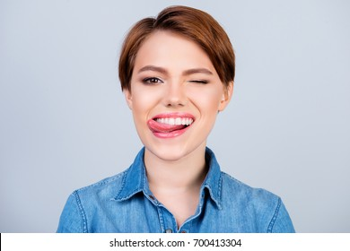 Close up portrait of happy pretty young girl with short hair and jeans shirt licking lips and giving a wink
