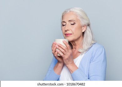 Close up portrait of happy satisfied joyful cheerful peaceful calm mature woman with grey hair and closed eyes, she is enjoying fresh coffee in her hands, isolated on gray background, copy-space