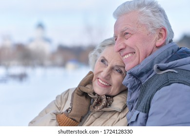 Close up portrait of happy senior couple hugging at winter outdoors