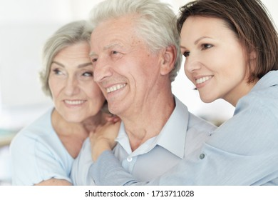 Close up portrait of happy senior parents with daughter at home