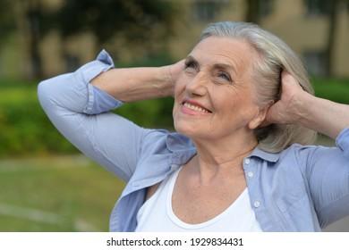 Close up portrait of happy senior woman in autumn park