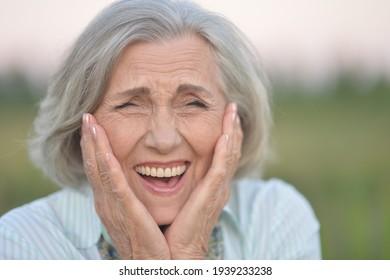 Nahaufnahme eines Porträts glücklicher älterer Frau im Park