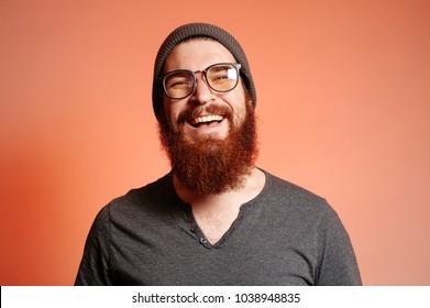 Nahaufnahme des Porträts eines glücklichen, lächelnden, bärtigen Hipster-Mannes mit Brille und selbstbewusster Betrachtung der Kamera