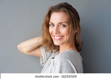 Close up portrait of a happy smiling beautiful woman posing with hand in hair against gray background