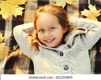 Close up portrait of happy smiling little girl child lying on a plaid with yellow maple leaves in autumn day top view