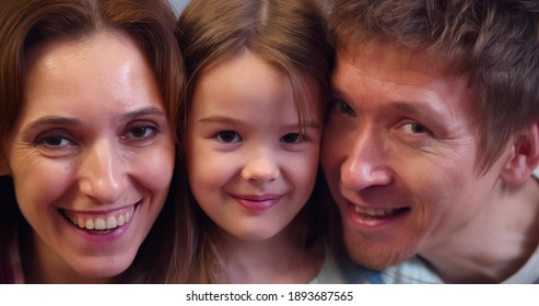 Close up portrait of happy smiling mother, father and little daughter. Headshot of loving young parents and preteen girl child looking at camera posing together