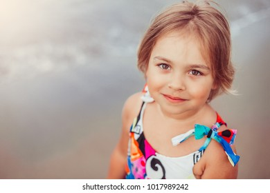 Close up portrait of happy smiling positive cute blondie caucasian girl on the beach coast. Kid having fun outdoors. Summer vacation and healthy lifestyle conceptPortrait of a cute little girl with a
