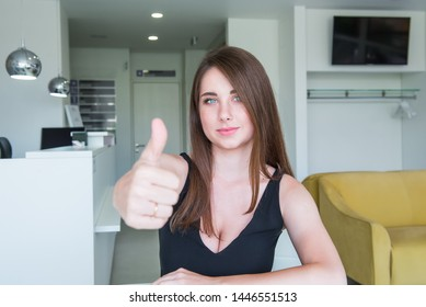 Close up Portrait of happy smiling young woman with deep decollete and thumb up hand sitting behind the desk in the office hall. Selective focus, copy space