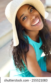 Close up portrait of a happy smiling young woman with sun hat