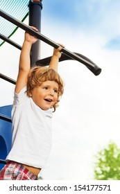 Close portrait of happy three years old boy about to hand on the horizontal bar on playground