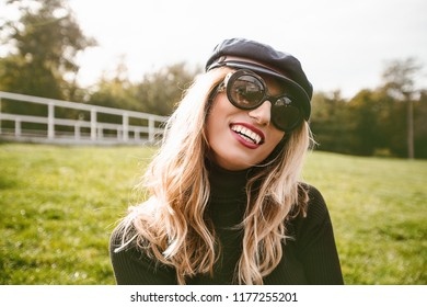 Close up portrait happy woman in sunglasses and stylish cap in a autumn park, romantic, red lips, pretty, attractive, laughing, coat, holding twig, stylish, jeans, cap, sunglasses, hipster girl