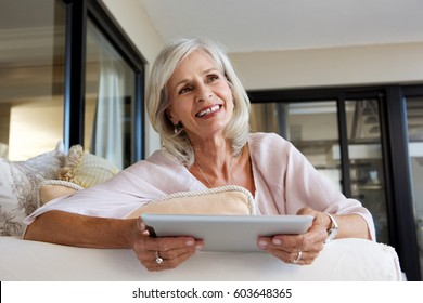Close up portrait of happy woman with touch screen tablet at home