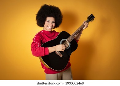 Close up portrait of happy young african american woman laughing with guitar