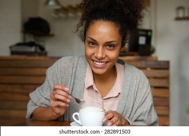 Close up portrait of a happy young african american woman with cup of coffee