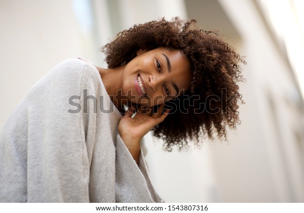 Close up portrait of happy young african american woman with curly hair smiling outside