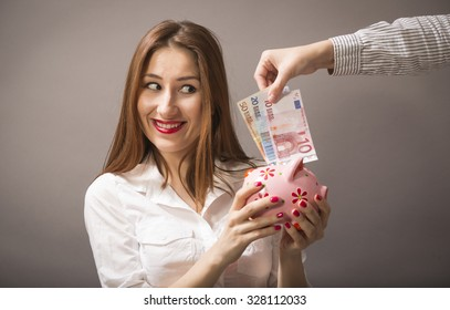 Close up portrait of happy young beautiful woman with pink piggy bank and another person hand putting money in it, studio shot on gray background. Safe savings. Business investment growth concept