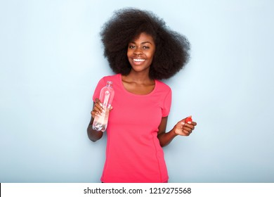 Close up portrait of happy young black woman holding bottle of water