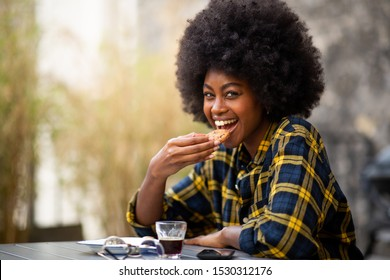 Close up portrait of happy young black woman eating cookie