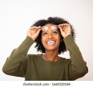 Cierra el retrato de una joven negra feliz con anteojos mirando hacia el fondo blanco aislado