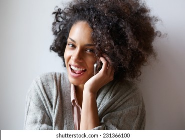 Close up portrait of a happy young black woman talking on mobile phone