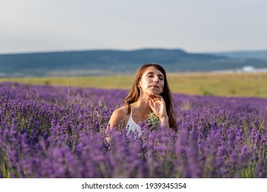 Close up portrait of happy young brunette woman in white dress on blooming fragrant lavender fields with endless rows. Warm sunset light. Bushes of lavender purple aromatic flowers on lavender fields.