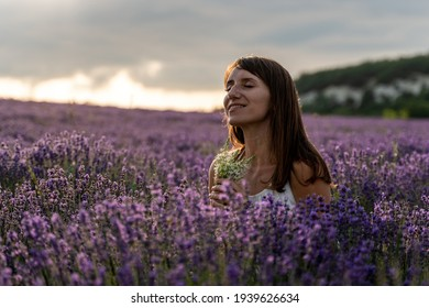 Close up portrait of happy young brunette woman in white dress on blooming fragrant lavender fields with endless rows.