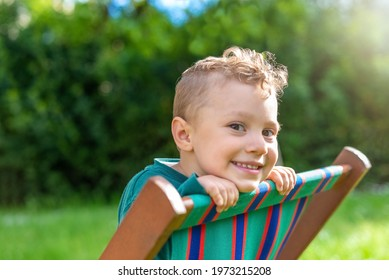 close up portrait of a happy young kid standing on deckchair outdoor looking at the camera smiling. side view of a child chilling in a public park garden relaxing. joy happiness. sunlight effect