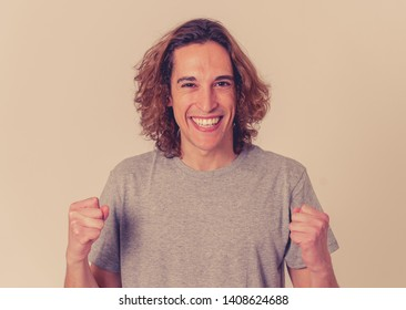 Close up portrait of happy young man with long hair wearing white T-shirt. Smiling feeling satisfied and confident. With copy space. People, positive human facial expressions and emotions concept.