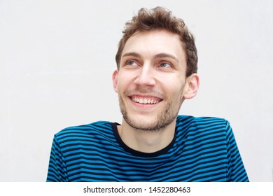Close up portrait of happy young man smiling and looking up by isolated white background