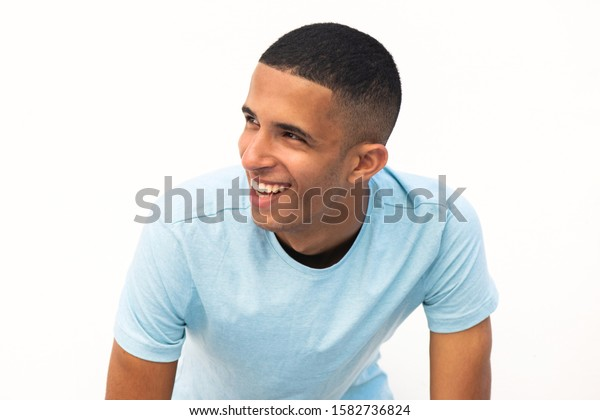 Close up portrait of happy young North African man looking away by white background