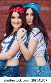 Close up portrait of happy young twins girls, wearing bright bandanas, hugging. Brick urban wall background.