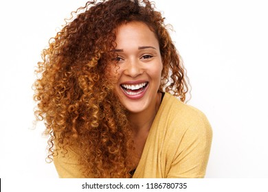 Close up portrait of happy young woman with curly hair laughing against white background