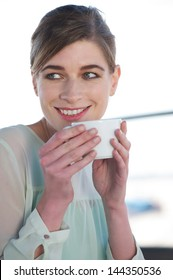 Close up portrait of a happy young woman drinking a cup of coffee outdoors