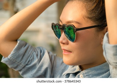 Close up portrait happy young woman tied her hair , Look fun with her heart glasses , Warn Summer Style color.