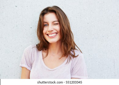 Close up portrait of happy young woman smiling and winking against gray wall