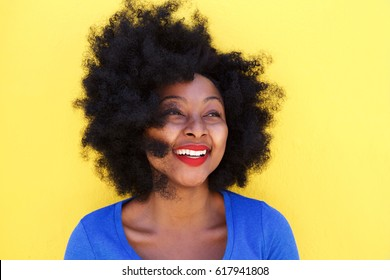 Close up portrait of happy young woman with afro hair smiling